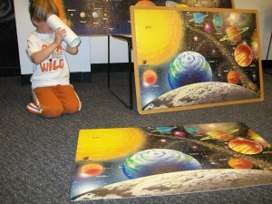Mommy and Zander put a puzzle of the solar system together. Zander is looking into space with his telescope he made.