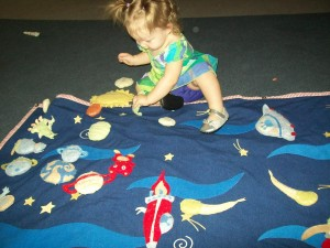 Lexi found a play mat with solar system shaped pillows to play with.  She had fun complete with automobile noices.